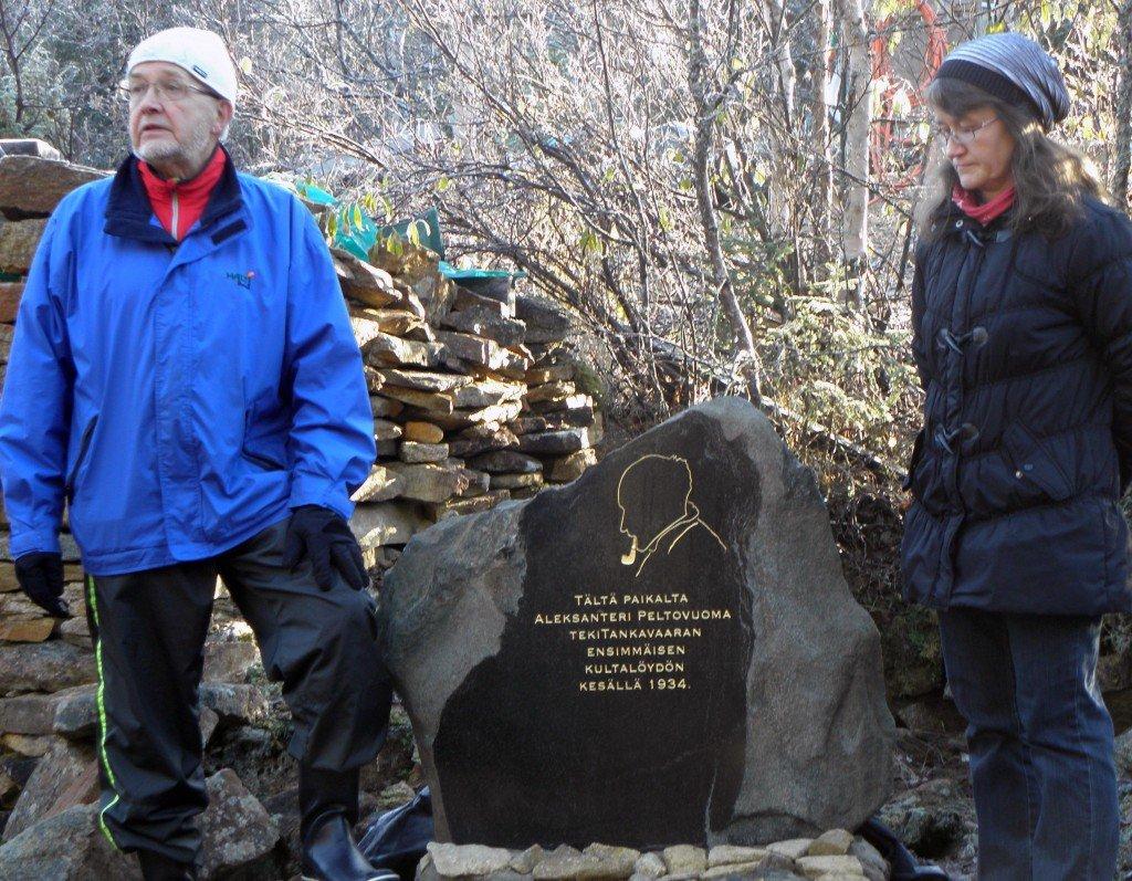 Museojohtaja Heli Heinäaho ja tietokirjailija Seppo J. Partanenpaljastavat patsaan Tankavaaran kullan löytöpaikalla. Taustalla näkyy tämän päivän kullankaivuvälineistöä.